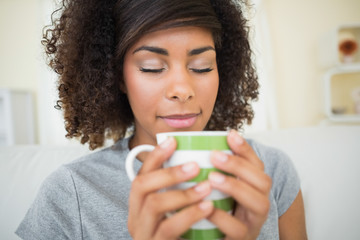 Pretty content brunette smelling a mug of coffee