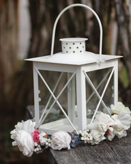 lantern with bridal wreath on wooden table