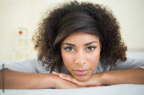 Pretty unsmiling brunette lying on bed resting head on hand