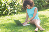 Gorgeous focused brunette sitting on grass using laptop