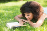 Gorgeous happy brunette lying on grass reading book