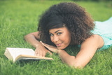 Gorgeous lucky brunette lying on grass reading book