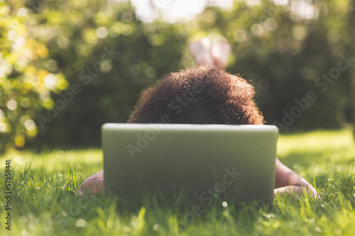 Brunette lying on grass using laptop