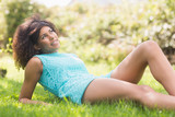 Gorgeous pensive brunette lying on grass