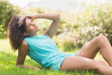 Gorgeous thoughtful brunette lying on grass