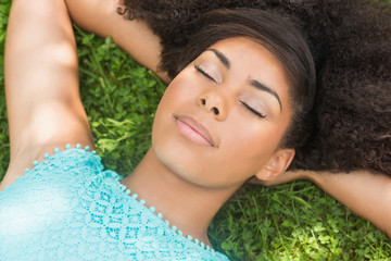 Peaceful gorgeous brunette lying on grass with closed eyes