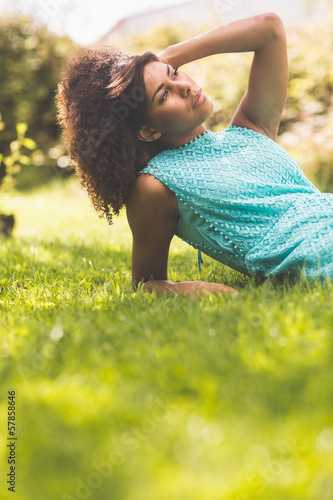 Gorgeous thoughtful brunette lying on grass touching head
