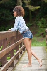 Gorgeous serious brunette leaning against bridge