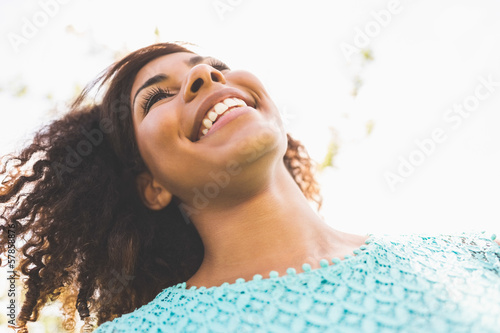 Gorgeous laughing brunette standing in sunlight