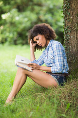 Gorgeous unsmiling brunette reading under tree