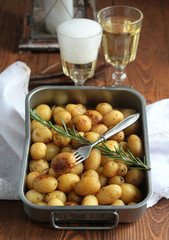 potatoes baked with herbs at the festive table with champagne