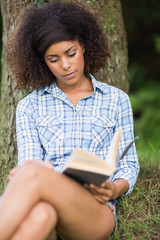 Gorgeous peaceful brunette reading under tree