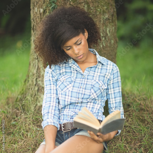 Gorgeous serious brunette leaning against tree reading