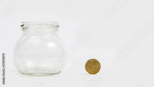 pound coin by empty jar