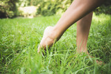 Close up of female bare feet standing on grass