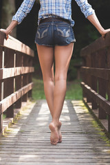 Rear view of lower body of model walking on bridge