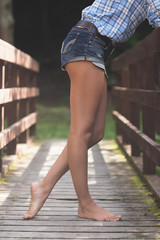 Side view of lower body of model leaning against bridge
