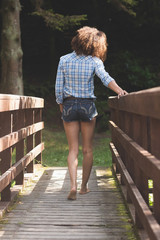 Rear view of gorgeous brunette walking on bridge