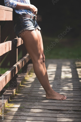 Lower body of model standing on bridge