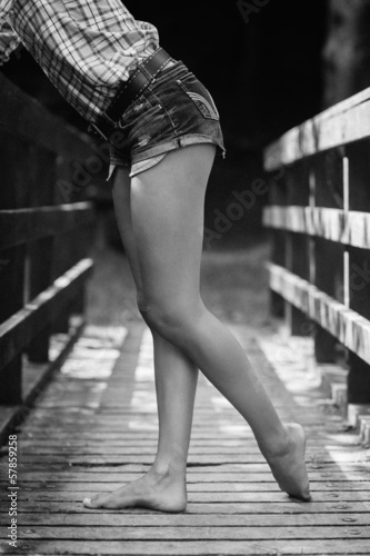 Side view of lower body of model leaning against bridge in black and white