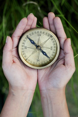 Hands holding old style antique compass