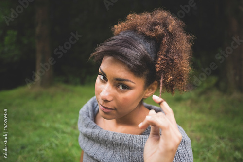 Portrait of gorgeous content brunette holding lock of hair
