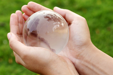 Hands holding a glass globe