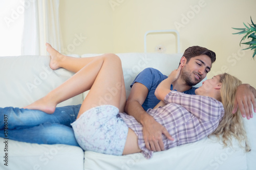 Loving content couple cuddling on couch