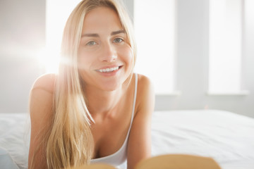 Cheerful blonde reading a book on her bed