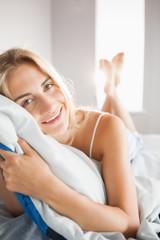 Happy blonde hugging her pillow