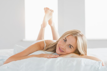 Happy blonde lying on her pillow