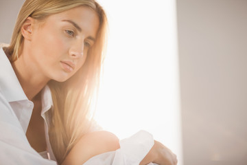 Pretty blonde wearing white mens shirt sitting on bed