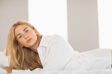 Sensual blonde wearing white mens shirt lying on bed looking at camera