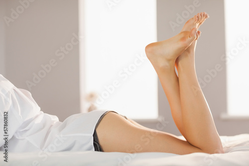 Woman wearing white mens shirt lying on bed