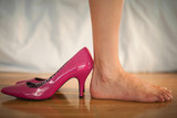 Woman standing beside fun pink high heels