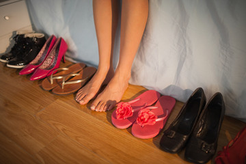 Woman sitting on edge of bed beside wide variety of shoes