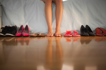 Woman sitting on edge of bed beside large variety of shoes