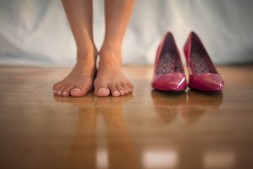 Woman standing beside pink high heels