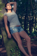 Gorgeous ponytailed woman posing leaning against a tree