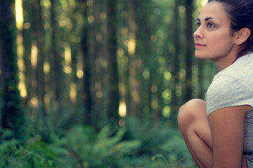 Attractive brunette woman sitting in a forest