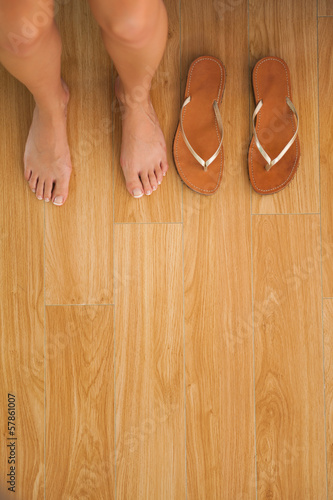 Woman sitting on edge of bed beside her sandals