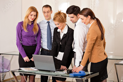 business woman with colleagues looking at laptop