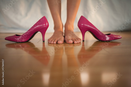 Woman standing beside bright pink high heels