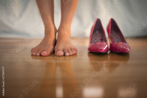 Woman standing beside pink high heels