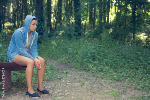 Young casual woman sitting on a bench in a forest