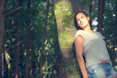 Cute casual woman leaning against a tree