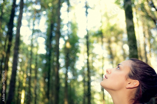 Fascinated young woman sitting in the middle of a forest