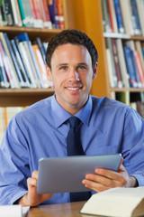 Smiling librarian sitting at desk using tablet