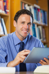 Happy librarian sitting at desk using tablet