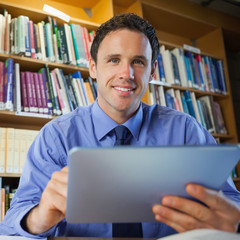 Handsome librarian sitting at desk using tablet